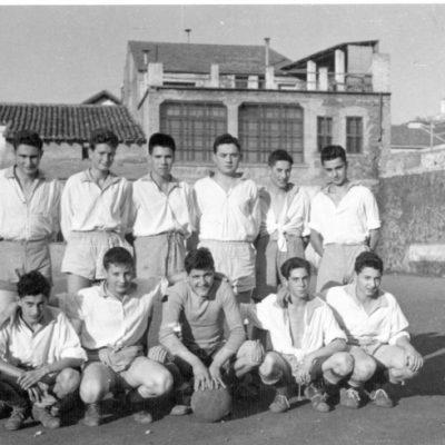 Retrat de grup de cos sencer de l'equip de futbol del Casal Marià, d'Olot, al seu camp de futbol.