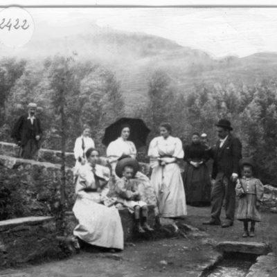 Reproducció d'un retrat de grup de cos sencer d'una família al pont del Molí del Collell, avui desaparegut, a Olot.