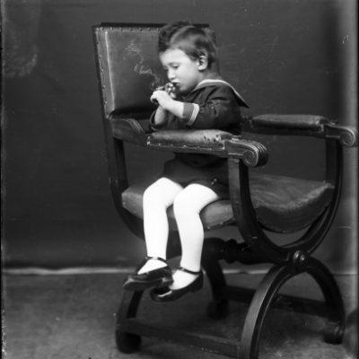 Retrat de cos sencer d'un nen fumant.