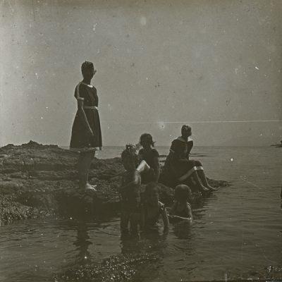 Retrat de cos sencer de tres dones de la família Bassols i els nens Dolors, Xavier i Joan Montsalvatge, a la platja, a Llançà.