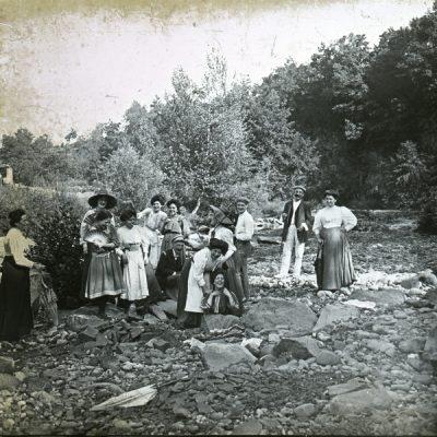 Retrat de grup de cos sencer de diversos membres de la família Bassols, vora un riu. Al centre, assegut, en segon terme, l'advocat Joan Bassols, i, a la dreta, amb barret, la seva filla Mercè Bassols.