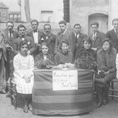 Comissió organitzadora de la diada de Sant Jordi en una parada de clavells davant del convent dels caputxins. ACGAX. Servei d'Imatges. Col·lecció d'imatges de Josep M. Dou Camps. Autor desconegut, 1921.