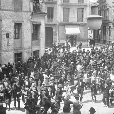 Ballada de sardanes davant del local del Casal Català, a la plaça d'Esteve Ferrer, durant la diada de Sant Jordi. ACGAX. Servei d'Imatges. Col·lecció d'imatges de Josep M. Dou Camps. Autor desconegut, 1921.