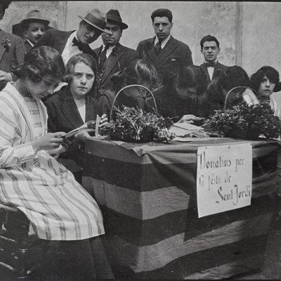 Comissió organitzadora de la diada de Sant Jordi en una parada de clavells davant del convent dels caputxins. ACGAX. Servei d'Imatges. Fons Josep M. Melció Pujol. Autor desconegut, 1921.