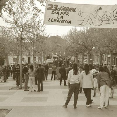 Acte de la campanya 'El català, cosa de tots', al passeig de Miquel Blay, o Firal, durant la diada de Sant Jordi. ACGAX. Servei d'Imatges. Col·lecció L'Abans. Cessió de Pep Roura Bendicho. Autor: Pep Roura Bendicho, 1982.