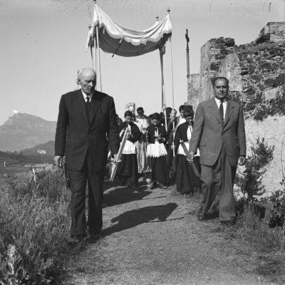 Vista parcial de la processó de Corpus dalt del volcà del Montsacopa. En primer terme, Rafael Arau i el seu fill Joan Arau. En segon terme, la custòdia sota pal·li amb mossèn Salvador Bassas i mossèn Llorenç Pascuet. ACGAX. Servei d'Imatges. Fons Àngel Noguera Magrià. Autor: Àngel Noguera Magrià, 1954.