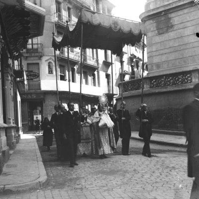 Vista parcial de la processó de Corpus a la plaça d'Esteve Ferrer. Al centre, la custòdia sota pal·li i, al fons, la merceria can Tenas. ACGAX. Servei d'Imatges. Fons Àngel Noguera Magrià. Autor: Àngel Noguera Magrià, 1954.
