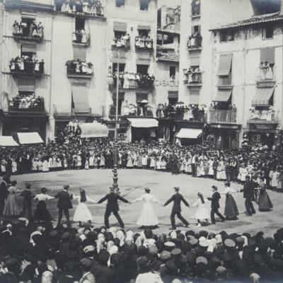 Vista parcial de la plaça Major d'Olot durant la ballada de la sardana de Corpus. ACGAX. Servei d'Imatges. Fons Josep Berga i Boix. Autor desconegut, c.1900.