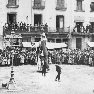 Vista parcial de la plaça Major d'Olot durant el ball dels Gegants del dia de Corpus. En primer terme, el fanal de petroli que il·luminava la plaça. ACGAX. Servei d'Imatges. Col·lecció d'imatges de Josep M. Dou Camps. Autor: Vicenç Grivé Coma, 1890.