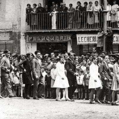 Vista parcial del passant de les parelles participants a la sardana de Corpus, a la plaça Major. ACGAX. Servei d'Imatges. Col·lecció L'Abans. Cessió d'Anna Montañá Gratacós. Autor: Emeteri Vélez Valls, 1928.