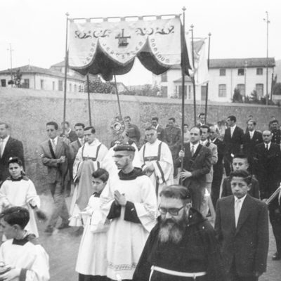 Vista parcial de la processó celebrada a Olot pels frares caputxins amb motiu de l'octava de Corpus, al seu pas per la ronda del Fluvià. En segon terme, la custòdia sota pal·li. ACGAX. Servei d'Imatges. Col·lecció d'imatges de Josep M. Dou Camps. Autor desconegut, c.1950.