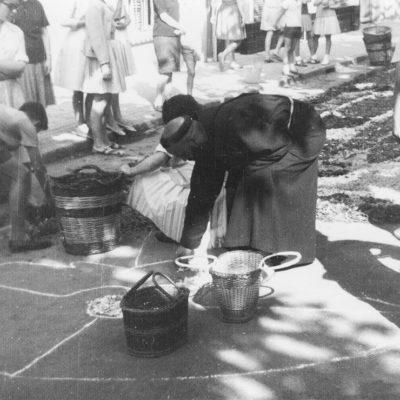 Vista parcial de l'elaboració de la catifa de flors del pare Marià d'Olot, caputxí, al centre, el dia de Corpus. ACGAX. Servei d'Imatges. Col·lecció d'imatges de Josep M. Dou Camps. Autor: Josep M. Dou Camps, 1962.