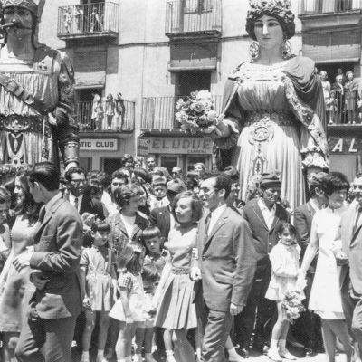 Vista parcial del passant de les parelles participants a la sardana de Corpus, a la plaça Major. En segon terme, els Gegants. ACGAX. Servei d'Imatges. Col·lecció d'imatges de Josep M. Dou Camps. Autor: Josep M. Dou Camps, 1969.