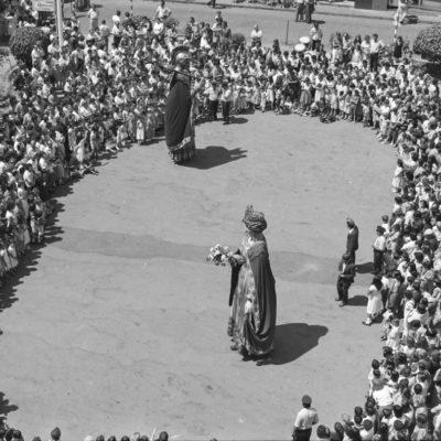 Vista general en contrapicat del ball dels gegants durant el dia de Corpus, a la plaça Major. ACGAX. Servei d'Imatges. Col·lecció L'Abans. Cessió de Pep Roura Bendicho. Autor: Pep Roura Bendicho, 1981.