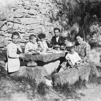 Retrat de la família Jaume Asperó menjant. D'esquerra a dreta, Ramon, Vicenç, Palmira, Francesc, Joan i Estanislau Jaume, i Faustina Asperó. ACGAX, Francesc Jaume Coll (Mestres), 1925